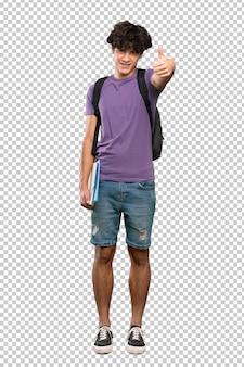Jonge student man met duimen omhoog omdat er iets goeds is gebeurd