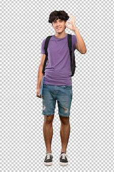 Jonge studentenmens die ok teken met vingers tonen