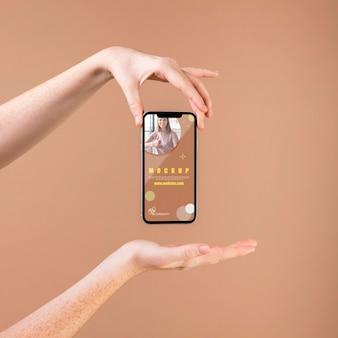 Jonge vrouw die een smartphonemodel houdt