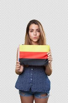 Jonge vrouw die een vlag van duitsland op wit houdt