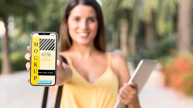 Jonge vrouw die haar telefoonmodel toont