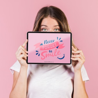 Jonge vrouw die het gezicht tot de ogen bedekt met een tabletmodel