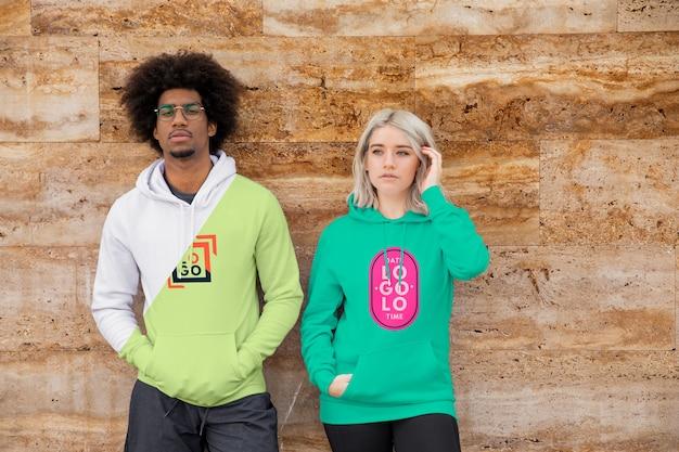 Jonge vrouw en man dragen hoodies