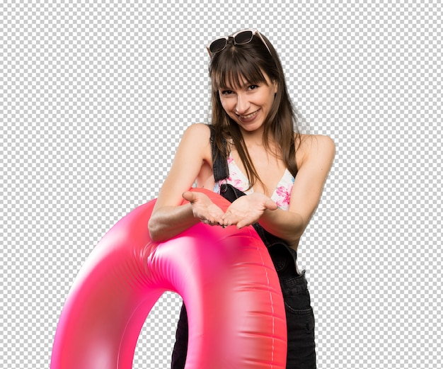 Jonge vrouw in bikini die copyspace denkbeeldig op de palm houdt om een advertentie in te voegen