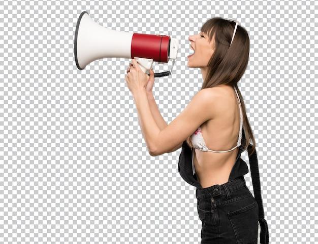 Jonge vrouw in bikini die door een megafoon schreeuwt