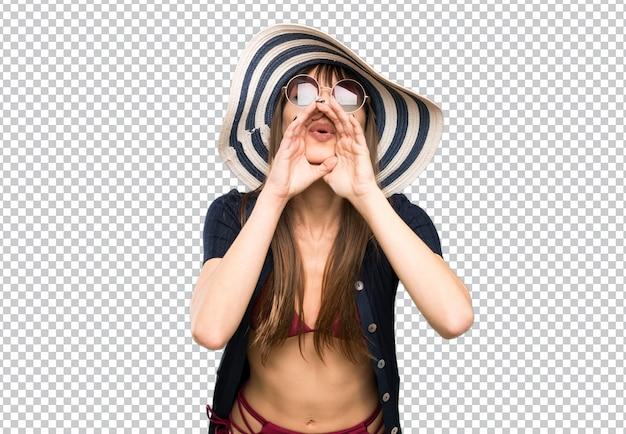 Jonge vrouw in bikini die met wijd open mond schreeuwen