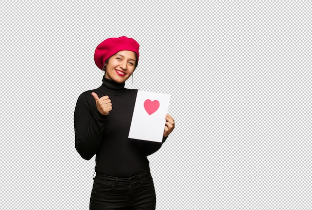 Jonge vrouw in valentijnsdag die en duim glimlacht opheft