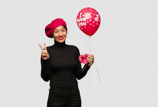 Jonge vrouw in valentijnsdag die nummer twee toont