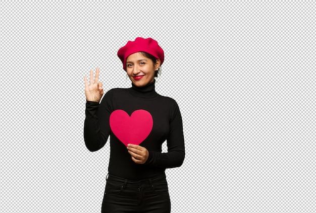 Jonge vrouw in valentijnsdag vrolijk en zeker die ok gebaar doet