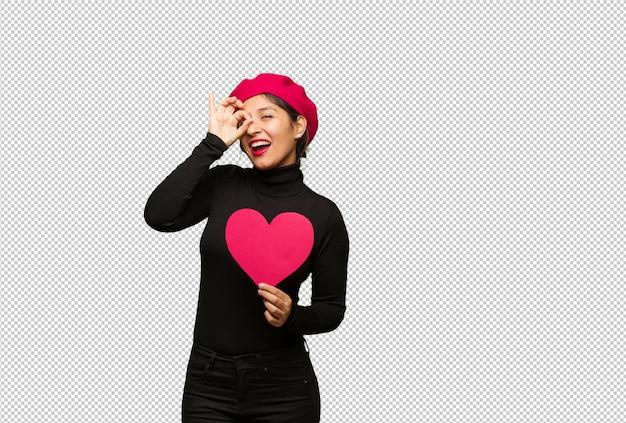 Jonge vrouw in valentijnsdag zeker doen ok gebaar op oog