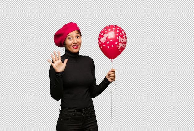 Jonge vrouw in valentijnskaartendag die nummer vijf tonen