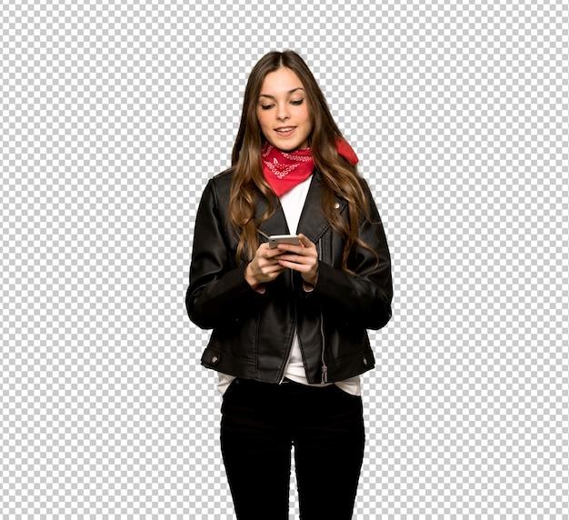 Jonge vrouw met lederen jas verzenden van een bericht met de mobiel