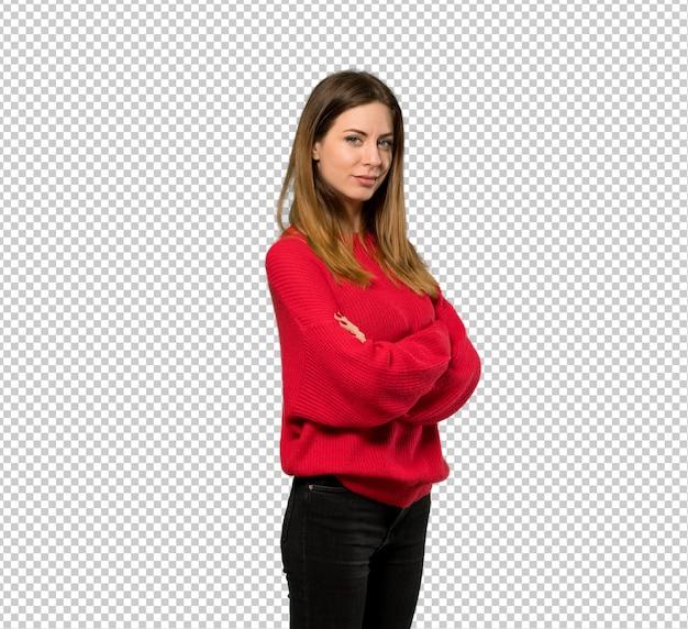 Jonge vrouw met rode trui met armen gekruist en kijkt uit