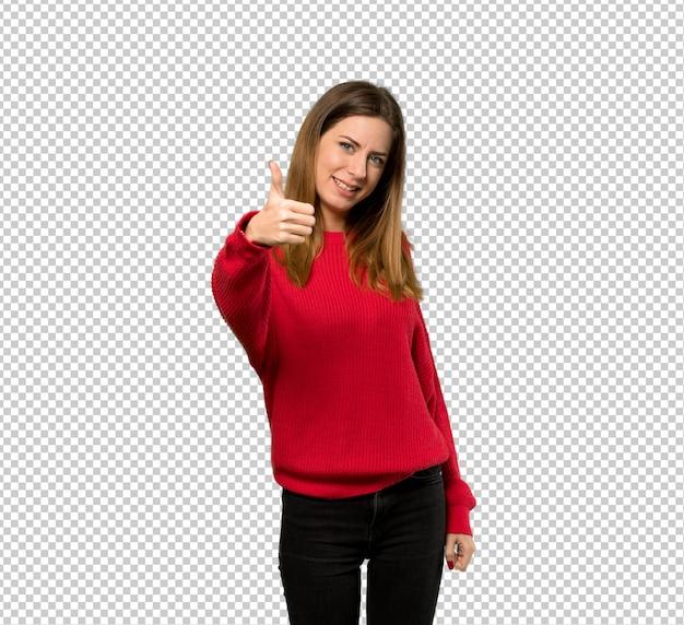 Jonge vrouw met rode trui met duimen omhoog omdat er iets goeds is gebeurd