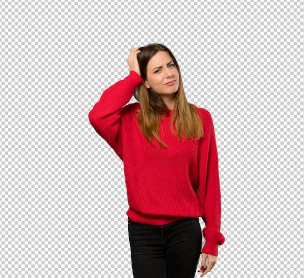 Jonge vrouw met rode trui met een uitdrukking van frustratie en niet begrijpen