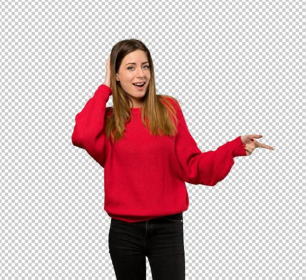 Jonge vrouw met rode trui verrast en wijzende vinger aan de zijkant