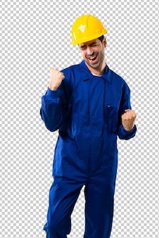 Jonge werkman met helm die een overwinning viert en gelukkig voor een prijs heeft gewonnen