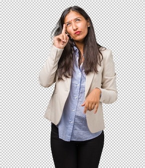 Jonge zakelijke indiase vrouw denken en opzoeken, verward over een idee, zou proberen een oplossing te vinden
