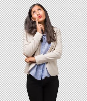 Jonge zakelijke indiase vrouw twijfelen en verward, denken aan een idee of bezorgd over iets
