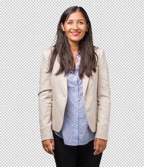 Jonge zakelijke indiase vrouw vrolijk en met een grote glimlach, zelfverzekerd, vriendelijk en oprecht, positiviteit en succes uitdrukken