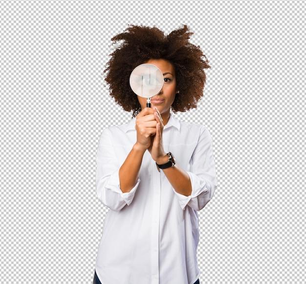 Jonge zwarte die door het vergrootglas kijkt