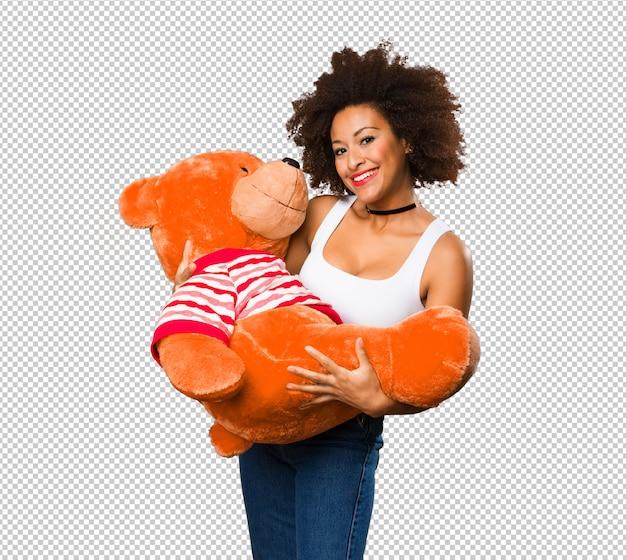 Jonge zwarte die een grote teddybeer houdt