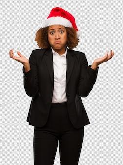 Jonge zwarte onderneemster die een hoed die van de kerstmissanta aan het twijfelen en schouders draagt draagt