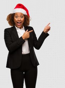 Jonge zwarte onderneemster die een hoed die van kerstmissanta draagt iets houdt met hand