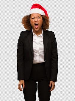 Jonge zwarte onderneemster die een hoed die van kerstmissanta dragen zeer zeer boos en agressief gilt