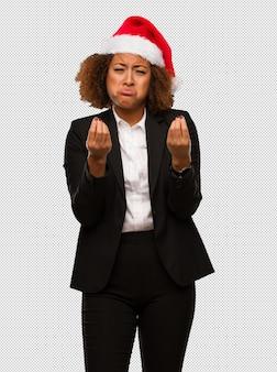 Jonge zwarte onderneemster die een hoed van kerstmissanta draagt die een gebaar van behoefte doet