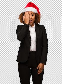 Jonge zwarte onderneemster die een kerstmishoed draagt die gelukkig en gezicht met hand behandelt schreeuwt