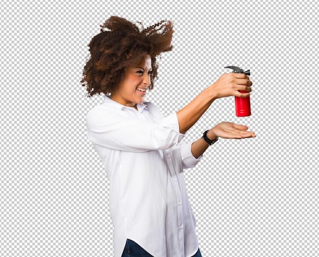 Jonge zwarte vrouw met behulp van een spray