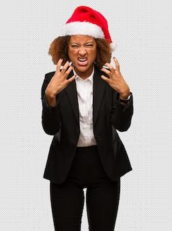 Jonge zwarte zakenvrouw, gekleed in een kerst-santa hoed boos en boos