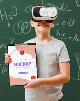 Jongen die virtuele werkelijkheidshoofdtelefoon met klembordmodel draagt