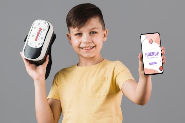 Jongen die virtuele werkelijkheidshoofdtelefoon met telefoonmodel houden
