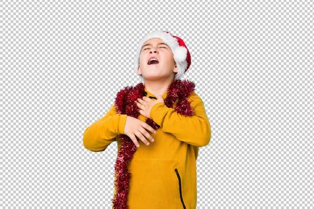 Jongetje vieren kerstdag draagt een kerstmuts lacht vrolijk en heeft plezier bij het houden van de handen op de buik.