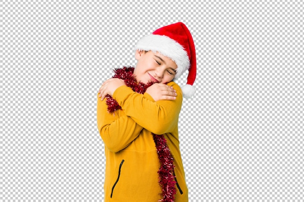 Jongetje vieren kerstdag dragen een kerstmuts geïsoleerd knuffels, zorgeloos en gelukkig glimlachen.