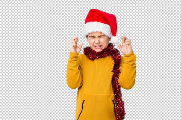 Jongetje vieren kerstdag dragen een kerstmuts geïsoleerd kruising vingers voor het hebben van geluk