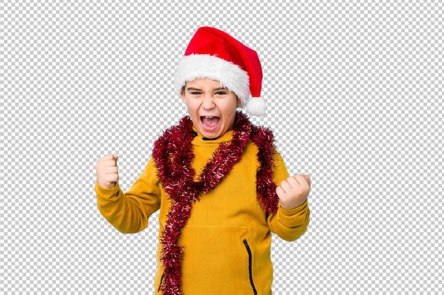 Jongetje vieren kerstdag dragen een kerstmuts geïsoleerd zorgeloos en opgewonden gejuich. overwinning concept.