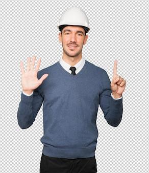 Joven arquitecto haciendo un gesto de número seis