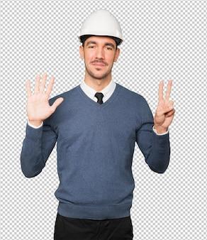 Joven arquitecto haciendo un gesto de número siete
