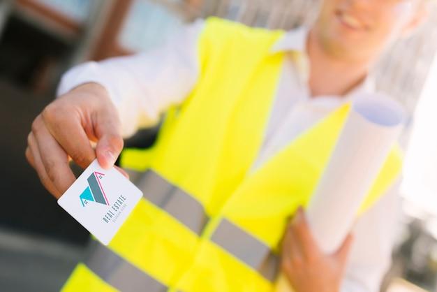 Joven arquitecto sosteniendo una maqueta de tarjeta de visita