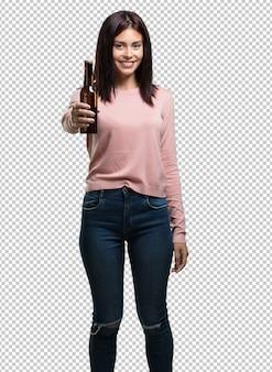 Joven y bella mujer feliz y divertida, sosteniendo una botella de cerveza, se siente bien después de un intenso día de trabajo, lista para ver un partido de fútbol en la televisión.