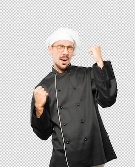 Joven chef competitivo haciendo un gesto de celebración