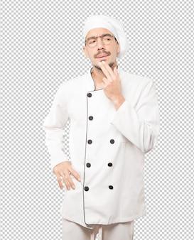 Joven chef concentrado haciendo un gesto de desconfianza