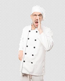 Joven chef enojado tratando de decir algo con fuerza