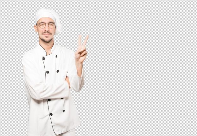 Joven chef haciendo un gesto número dos
