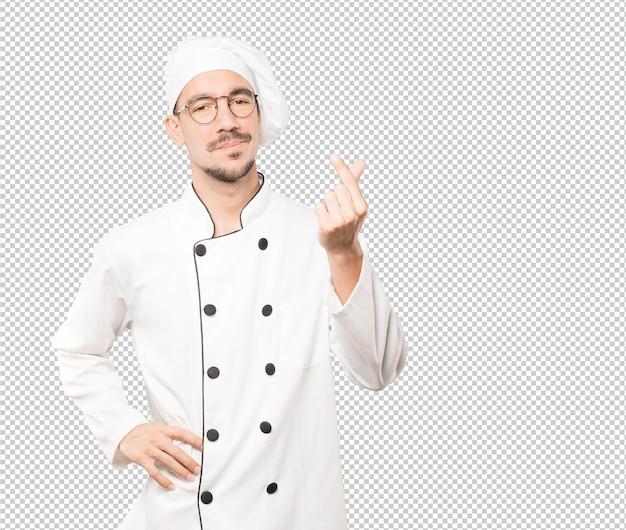 Joven chef haciendo un gesto de preocupación por su economía