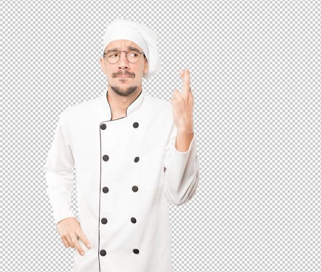 Joven chef preocupado haciendo un gesto de dedos cruzados