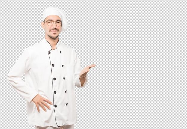 Joven chef saludando con la mano